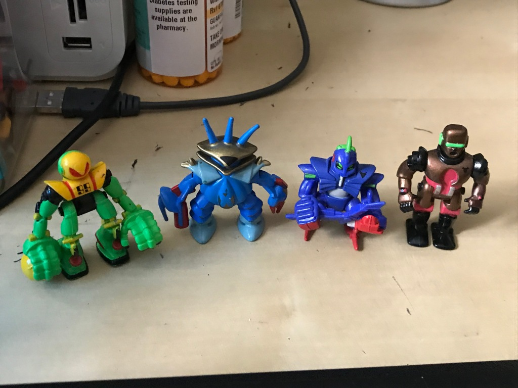 Four tiny robots, multicolored. One holds a yellow orb, another comes with a sword. One has a visor, and the other has a clawed hand and a cannon arm.